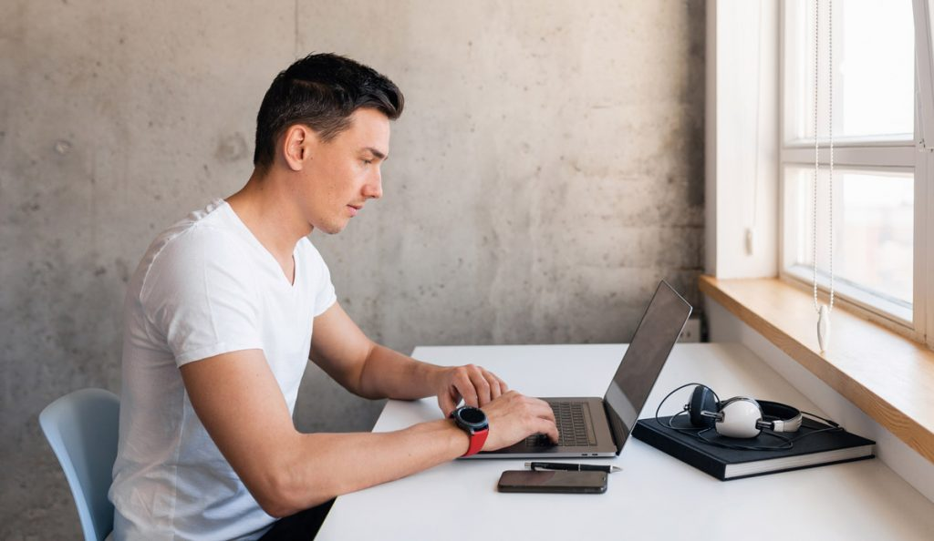 young handsome smiling man in casual outfit sitting at table working on laptop staying at home alone, typing, freelancer at work online.