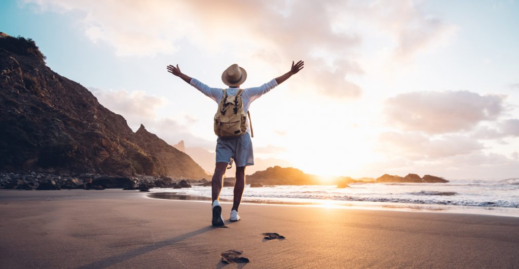 Young man arms outstretched by the sea at sunrise enjoying freedom and life, people travel wellbeing concept.