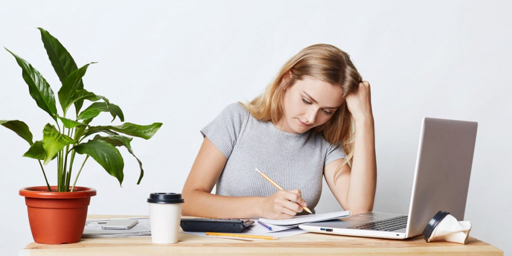 Portrait of serious blonde young businesswoman looking with pencil in her notebook.