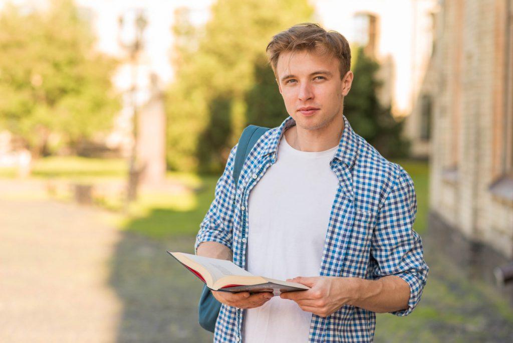 School boy with book in park.