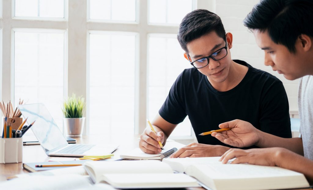 Learning, education and school concept. Young men studying for a test or an exam. Tutor books with friends. Young students campus helps friend catching up and learning.