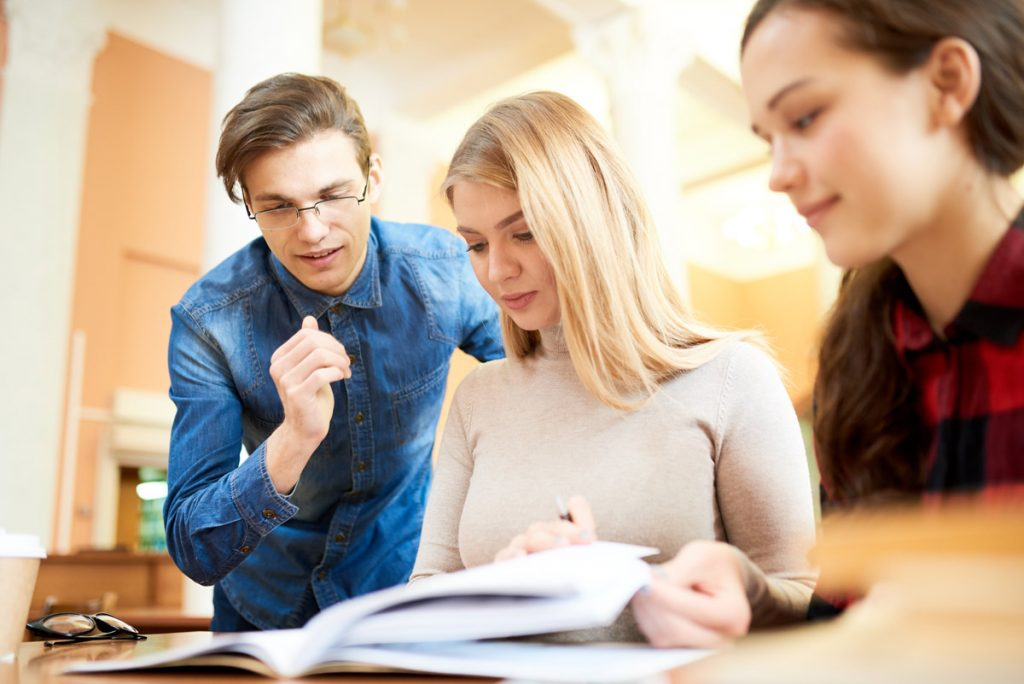 Positive confident handsome young male student explaining difficult topic to concentrated girls in modern library while they studying material together.