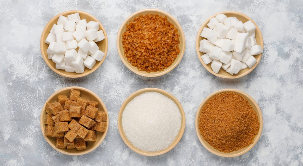 Various types of sugar, brown sugar and white on concrete ,top view.
