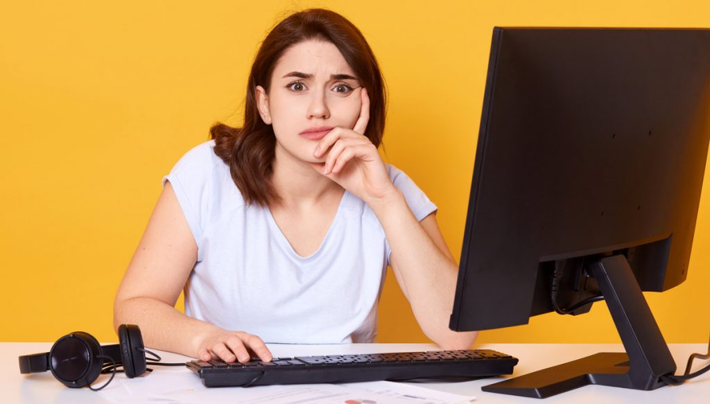 Close up portrait of pretty young female college student using desktop computer in a college library for writting report, has axuasted look, spends long hours in front display, keeps hand under chin.