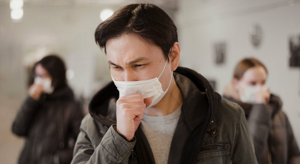 Front view of people with medical masks coughing.