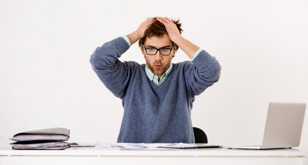 Handsome tired young businessman in glasses sitting at the office desk with hands over his head.