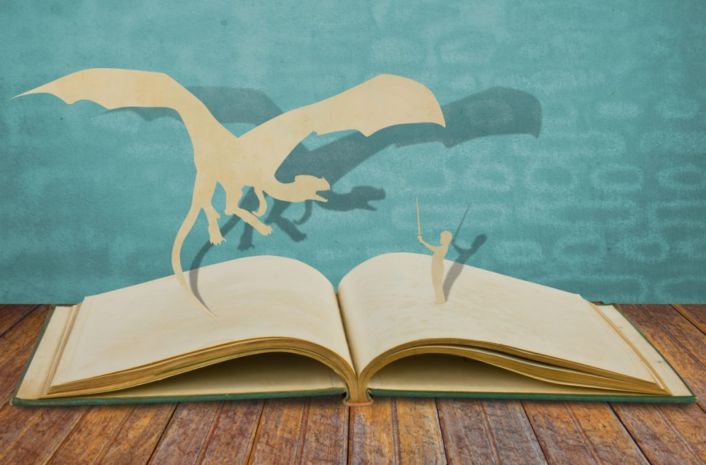 Paper cut of dragon and child hold sword on old book.