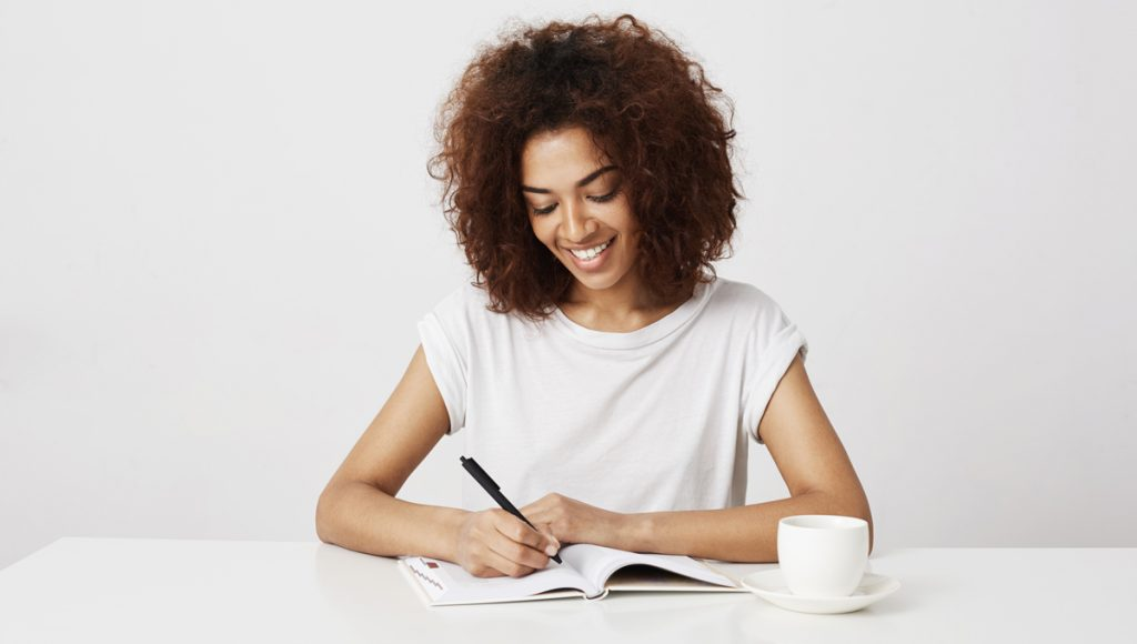 Cheerful african girl smiling writing in notebook at workplace over white background.