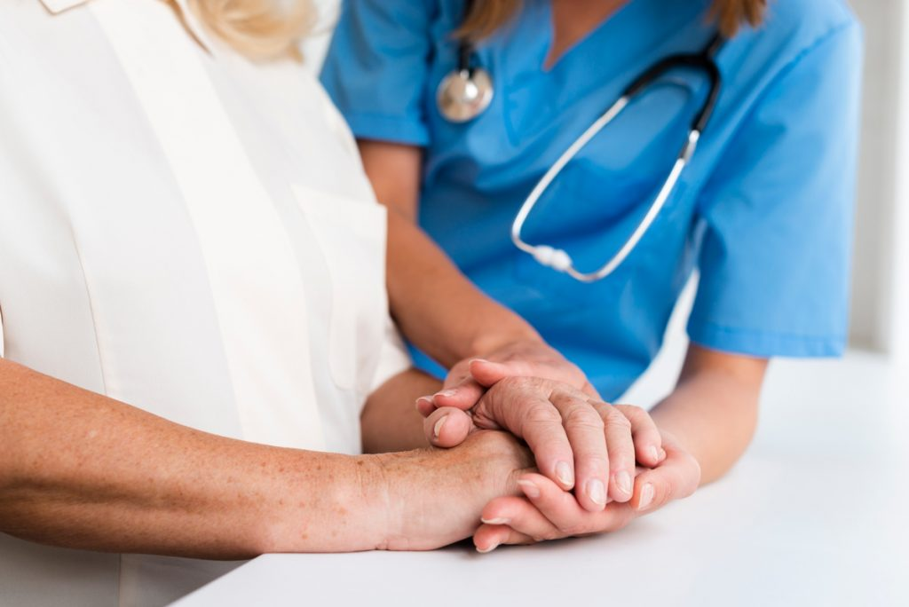 Doctor and old woman holding hands close-up.