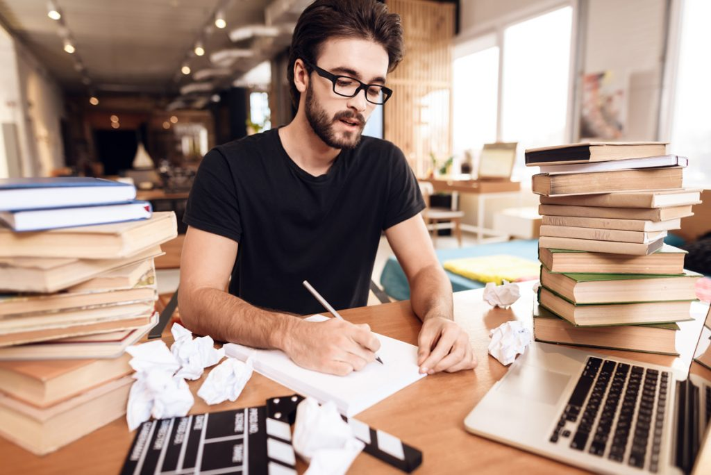 Freelancer bearded man in t-shirt taking notes sitting at desk surrounded by books.