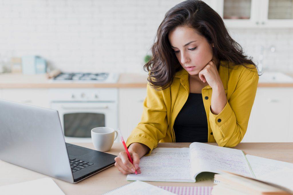 Medium shot woman with laptop writing.