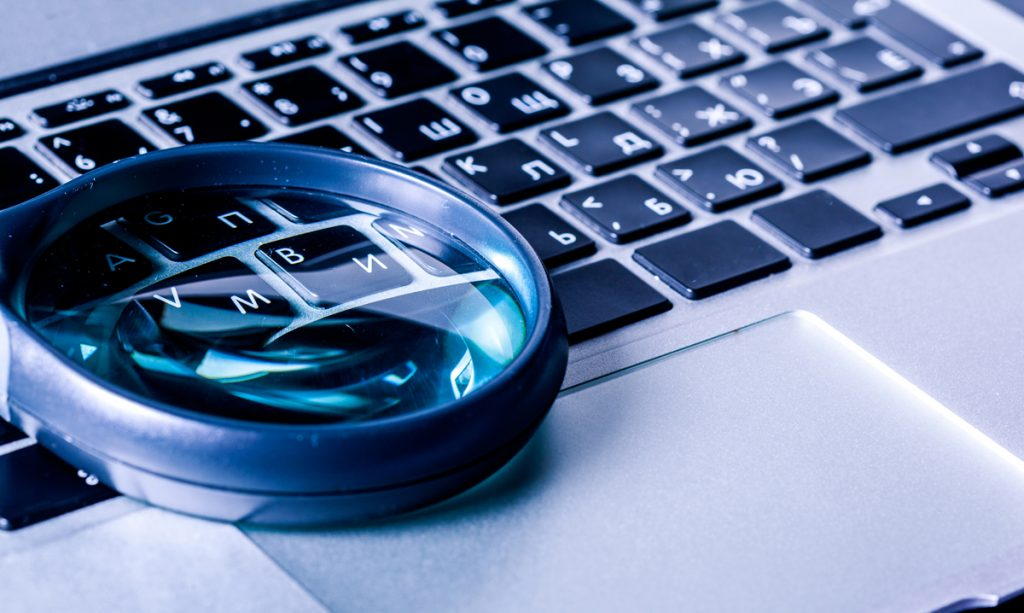 Closeup images of magnifying glass on laptop keyboard.