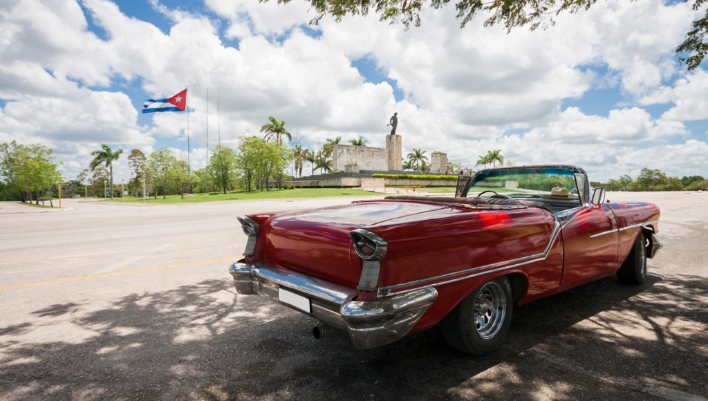 Classic convertible car with monument and cuban flag in background.