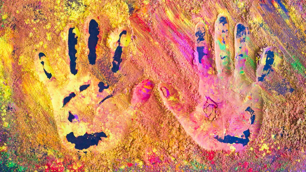 Hand prints on colourful powder.