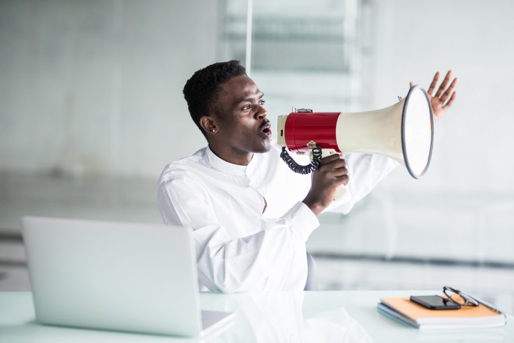 Afro businessman yelling through a megaphone in the office.