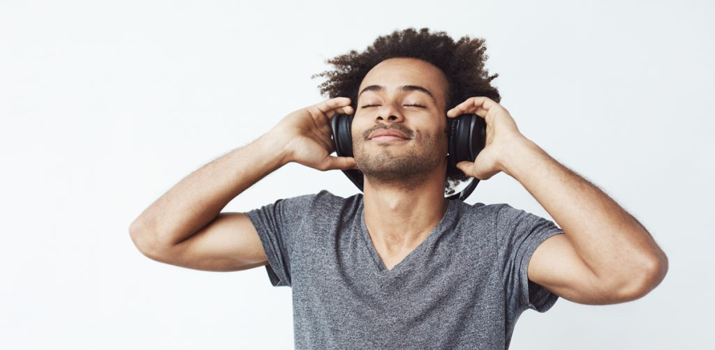 Happy african man smiling listening to music in headphones. White background. Closed eyes.