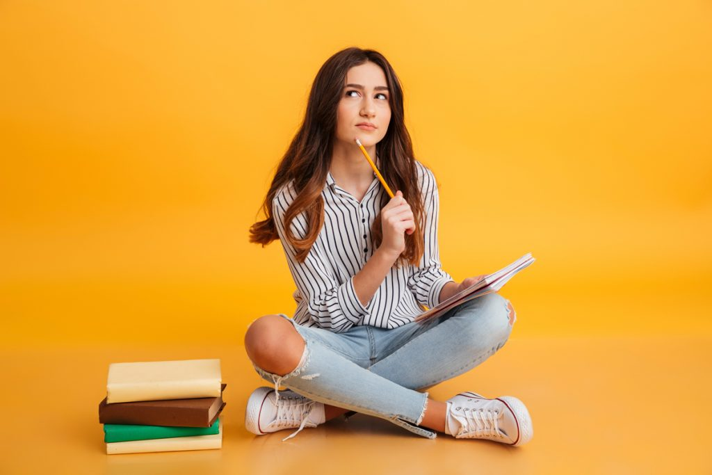 Portrait of a pensive young girl making notes while sitting with books isolated over yellow background.